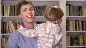 Νέος μπαμπάς που κρατά το γιο του και που δείχνει την άνω πλευρά, που πηδά και ενθαρρυντικός στη βιβλιοθήκη, χαμογελώντας και ευτ απόθεμα βίντεο