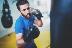Νέος μπόξερ που κάνει μερικών που εκπαιδεύουν punching στην τσάντα στη γυμναστική Γενειοφόρος καυκάσια κατάρτιση μπόξερ με punchi Στοκ φωτογραφίες με δικαίωμα ελεύθερης χρήσης