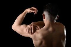 Νέος μυϊκός αθλητής που κρατά τον επώδυνο ώμο στον πόνο σχετικά με να τρίψει στην πίεση workout Στοκ εικόνες με δικαίωμα ελεύθερης χρήσης