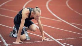 Νέος μυϊκός συγκεντρωμένος αθλητής στην έναρξη treadmill στο στάδιο φιλμ μικρού μήκους