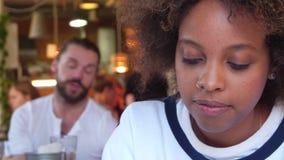 Νέος μόνος σπουδαστής μαύρων γυναικών Portret που συντρίβεται από την εργασία της στον καφέ Στους εύθυμους σπουδαστές ομάδας υποβ απόθεμα βίντεο
