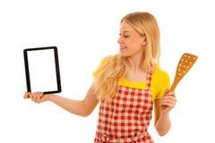 Νέος ξανθός αρχιμάγειρας γυναικών που παρουσιάζει ταμπλέτα με ένα recepy ove Στοκ εικόνες με δικαίωμα ελεύθερης χρήσης