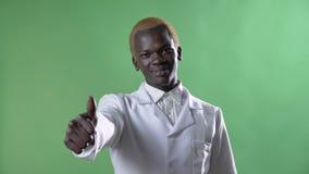 Νέος ξανθός γιατρός αφροαμερικάνων παλτό που παρουσιάζει όπως στη κάμερα, που απομονώνεται στο άσπρο στο υπόβαθρο chromakey, βέβα φιλμ μικρού μήκους