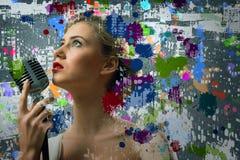 Νέος ξανθός θηλυκός τραγουδιστής με το μικρόφωνο Στοκ Φωτογραφίες