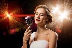Νέος ξανθός θηλυκός τραγουδιστής με το μικρόφωνο Στοκ φωτογραφία με δικαίωμα ελεύθερης χρήσης