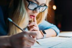 Νέος ξανθός καυκάσιος σπουδαστής eyeglasses που σκέφτονται και που γράφουν κάτι με το μολύβι Στοκ Εικόνα