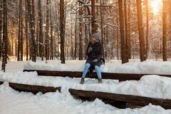 Νέος ξανθός σε ένα πλεκτό καπέλο, ένα μαντίλι και τα γάντια πίνει τον καφέ ή το τσάι καθμένος snowdrift το χειμώνα χιονισμένο στοκ φωτογραφίες με δικαίωμα ελεύθερης χρήσης