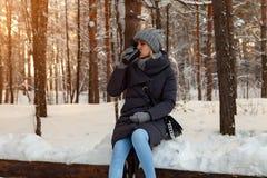 Νέος ξανθός σε ένα πλεκτό καπέλο, ένα μαντίλι και τα γάντια πίνει τον καφέ ή το τσάι καθμένος snowdrift το χειμώνα χιονισμένο στοκ εικόνες