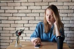 Νέος ξανθός στο μπλε πουκάμισο κάθεται στον πίνακα σε έναν καφέ στον οποίο στοκ εικόνα με δικαίωμα ελεύθερης χρήσης