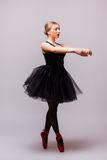 Νέος ξανθός χορός κοριτσιών ballerina και τοποθέτηση στα μαύρα παπούτσια tutu και μπαλέτου στο γκρίζο υπόβαθρο Στοκ εικόνες με δικαίωμα ελεύθερης χρήσης