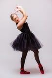 Νέος ξανθός χορός κοριτσιών ballerina και τοποθέτηση στα μαύρα παπούτσια tutu και μπαλέτου στο γκρίζο υπόβαθρο Στοκ Εικόνα