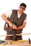 Νέος ξυλουργός που τρυπά μια τρύπα ξύλινο slat που απομονώνεται με τρυπάνι άνω του W Στοκ φωτογραφία με δικαίωμα ελεύθερης χρήσης