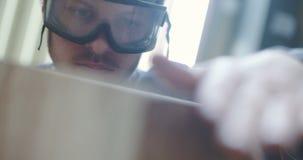 Νέος ξυλουργός στα προστατευτικά γυαλιά που εξετάζει το ξύλο απόθεμα βίντεο