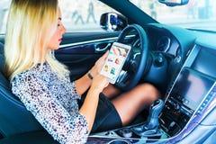 Νέος οδηγός γυναικών που χρησιμοποιεί έναν υπολογιστή ταμπλετών στο αυτοκίνητο Στοκ Εικόνα