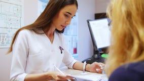 Νέος οδοντίατρος γυναικών που βγάζει φύλλα μέσω του υπομονετικού ιατρικού βιβλίου ` s Ο ασθενής κάθεται μπροστά από το γιατρό απόθεμα βίντεο