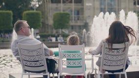 Νέος οικογενειακός μπαμπάς, mom και λίγη κόρη που στηρίζονται κοντά στην πηγή στο θερινό πάρκο απόθεμα βίντεο