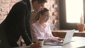 Νέος οικότροφος γραφείων που εργάζεται στο lap-top, εκτελεστική διδασκαλία, που δίνει τις οδηγίες φιλμ μικρού μήκους