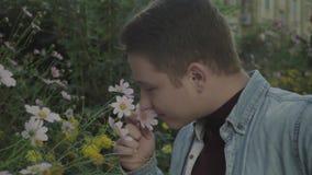 Νέος ομοφυλόφιλος που απολαμβάνει τη μυρωδιά των λουλουδιών απόθεμα βίντεο