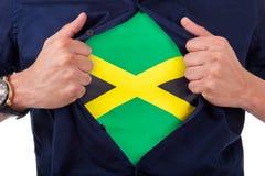 Νέος οπαδός αθλήματος που ανοίγει το πουκάμισό του και που παρουσιάζει στη σημαία αρίθμησή του Στοκ εικόνα με δικαίωμα ελεύθερης χρήσης