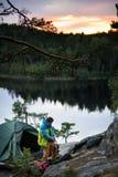 Νέος ορειβάτης που έχει ένα στρατόπεδο σε μια κορυφή ενός απότομου βράχου, μια γραφική λίμνη στο υπόβαθρο ηλιοβασιλέματος Στοκ Εικόνα