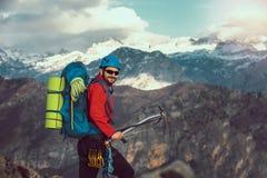 Νέος ορεσίβιος που στέκεται με το σακίδιο πλάτης πάνω από ένα βουνό Στοκ Εικόνες