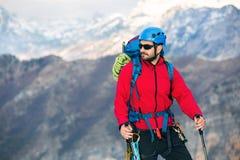 Νέος ορεσίβιος που στέκεται με το σακίδιο πλάτης πάνω από ένα βουνό Στοκ εικόνες με δικαίωμα ελεύθερης χρήσης
