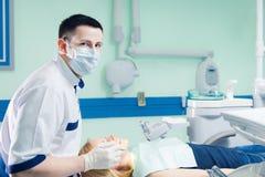 Νέος οδοντίατρος που συνεργάζεται με το θηλυκό ασθενή σε ένα σύγχρονο νοσοκομείο Στοκ φωτογραφία με δικαίωμα ελεύθερης χρήσης