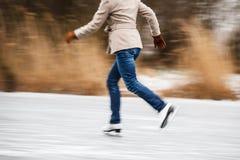 Νέος πάγος γυναικών που κάνει πατινάζ υπαίθρια σε μια λίμνη στοκ εικόνες