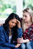 Νέος παρηγορώντας καταθλιπτικός θηλυκός φίλος γυναικών στο σπίτι Στοκ φωτογραφία με δικαίωμα ελεύθερης χρήσης