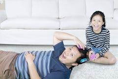 Νέος πατέρας και η κόρη του με τους κυλίνδρους τρίχας Στοκ Εικόνες