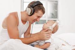 Νέος πατέρας με εννέα μηνών SOM του στο κρεβάτι στο σπίτι Στοκ Φωτογραφία
