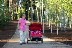 Νέος πατέρας με το δίδυμο καροτσάκι που περπατά στο πάρκο Στοκ Φωτογραφία