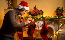 Νέος πατέρας που βάζει τα δώρα στις γυναικείες κάλτσες Χριστουγέννων στην εστία Στοκ φωτογραφίες με δικαίωμα ελεύθερης χρήσης