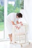 Νέος πατέρας που βάζει το νεογέννητο μωρό του στο παχνί Στοκ Φωτογραφία