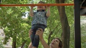 Νέος πατέρας που βοηθά το μικρό γιο του για να κάνει το τράβηγμα-UPS, εκπαιδευτικός γιος μπαμπάδων στο πάρκο, χαμόγελο απόθεμα βίντεο