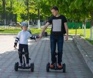 Νέος πατέρας που διδάσκει την κόρη του για να οδηγήσει hoverboard Στοκ Φωτογραφίες