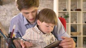 Νέος πατέρας που κρατά το μικρό γιο του, που κάθεται στον πίνακα και που γράφει σε χαρτί, σύγχρονο υπόβαθρο γραφείων απόθεμα βίντεο