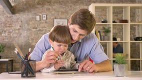 Νέος πατέρας που κρατά το μικρό γιο του και που γράφει σε χαρτί, ταμπλέτα εκμετάλλευσης παιδιών, συνεδρίαση στο σύγχρονο γραφείο απόθεμα βίντεο