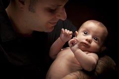 Νέος πατέρας που κρατά το μικτό νεογέννητο μωρό φυλών του Στοκ Εικόνες