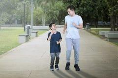 Νέος πατέρας που τρέχει με το γιο του στο πάρκο στοκ φωτογραφίες