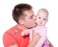 Νέος πατέρας που φιλά το ευτυχές μωρό Στοκ Εικόνα