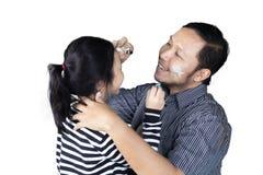 Νέος πατέρας που χρωματίζει ένα πρόσωπο της κόρης του Στοκ Εικόνες