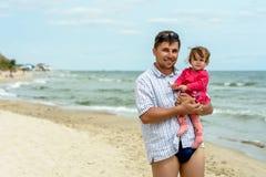 Νέος πατέρας στα γυαλιά ηλίου στην παραλία με μια μικρή κόρη στοκ εικόνες