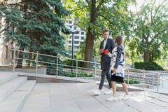 Νέος περίπατος ζευγών αγάπης γύρω από την πόλη με τον καφέ Στοκ εικόνες με δικαίωμα ελεύθερης χρήσης