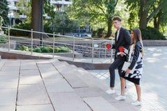 Νέος περίπατος ζευγών αγάπης γύρω από την πόλη με τον καφέ Στοκ φωτογραφία με δικαίωμα ελεύθερης χρήσης
