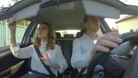 Νέος περιστασιακός ζευγών που ντύνεται παίρνει στο αυτοκίνητο και φεύγει στην εργασία το πρωί - απόθεμα βίντεο