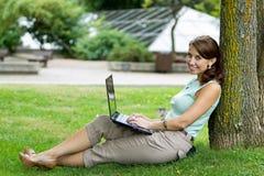 Νέος περιστασιακός σπουδαστής γυναικών στο πάρκο που λειτουργεί στο lap-top Στοκ φωτογραφία με δικαίωμα ελεύθερης χρήσης