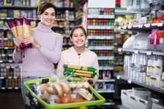 Νέος πελάτης γυναικών με το κορίτσι που ψάχνει τα ζυμαρικά στην υπεραγορά Στοκ εικόνες με δικαίωμα ελεύθερης χρήσης