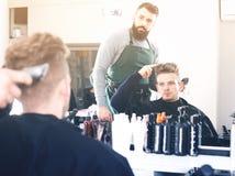 Νέος πελάτης που περιγράφει το επιθυμητό κούρεμά του Στοκ εικόνα με δικαίωμα ελεύθερης χρήσης