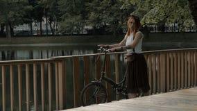 Νέος ποδηλάτης γυναικών που στέκεται σε μια λίμνη πόλεων γεφυρών στο θερινό πάρκο απόθεμα βίντεο